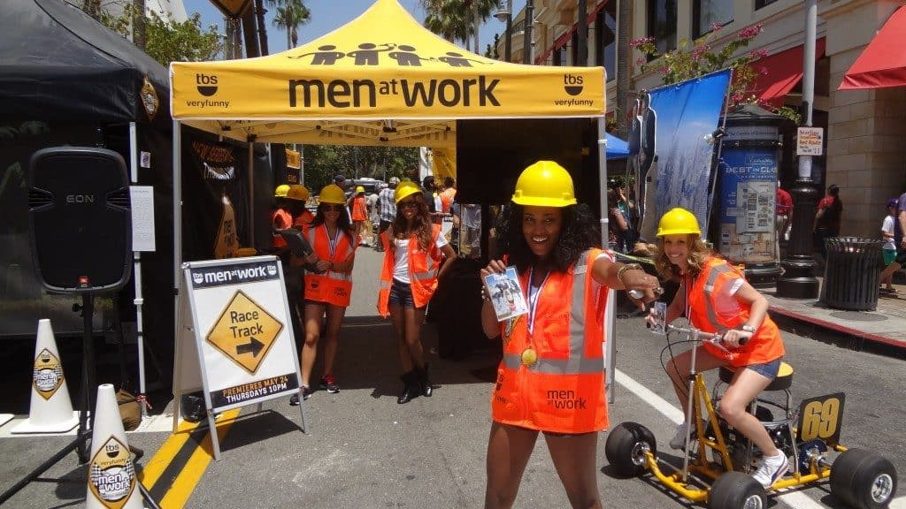 A women in construction gear promotes the TBS series, Men At Work